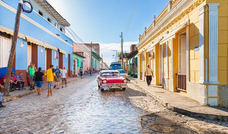 Trinidad, Cuba-October 14, 2016. View of busy street with historical colonial style buildings and cars, local people at their every day life in Trinidad town.