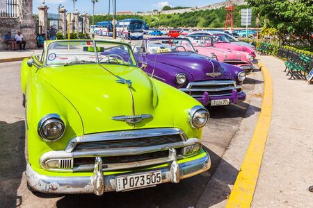 Havana, Cuba-October 07, 2016. Colorful, old classic American cars, used as Taxi, parked next to popular tourist attractions at old part of the Havana city.
