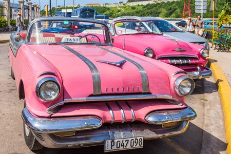 Havana, Cuba-October 07, 2016. Classic and old American cars, used as Taxi, parked next to popular tourist attractions at old part of the Havana city.