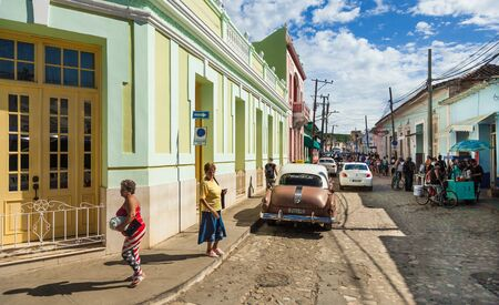 Trinidad, Cuba-October 14, 2016. View of busy street with historical colonial style buildings and cars, local people at their every day life in Trinidad town of Central Cuba.
