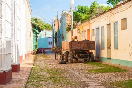 Trinidad, Cuba-October 14, 2016. Local cuban man is loading soil from trailer to his cart on the street with colorful historical colonial style buildings in Trinidad town of Central Cuba. Editorial