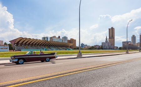 Havana, Cuba-October 07, 2016. View of the Malecon seafront street, skyline buildings of residential apartments and old stadium with the Casa de las Americas in the background in Havana City.