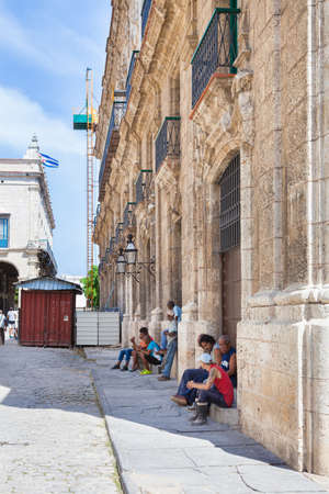 Havana, Cuba-October 7, 2016. View of Cuban men sitting on the street at historical Old Havana on October 7, 2016 in Cuba and it is part of Cubans life style.
