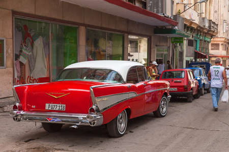 Havana, Cuba-October 7, 2016. Classic, old style American red car on the street and local people at every day life on October 07 2016, at old part of Havana City. Editorial