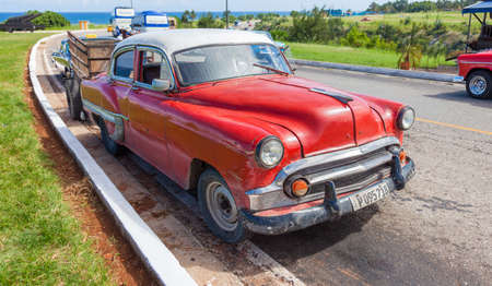 Havana, Cuba-October 7, 2016. Rusty and dirty old, classic American car with carriage parked by the sea at Old Havana on October 7, 2016 in Cuba.