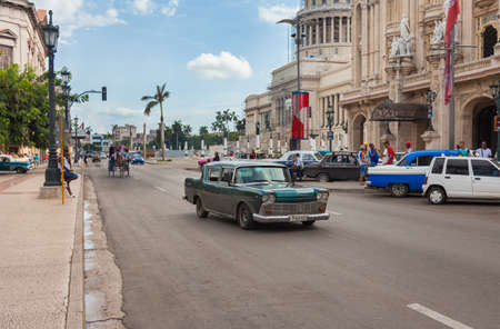 Havana, Cuba-October 07, 2016. Common and popular for tourist, busy street with classic, old style, American cars and people next to the historical, famous Great Theatre at old part of Havana City.