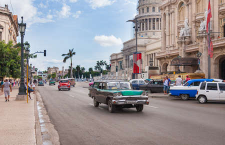 Havana, Cuba-October 07, 2016. Common and popular for tourist, busy street with classic, old style, American cars and people next to the historical, famous Great Theatre at old part of Havana City Editorial