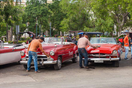 Havana, Cuba-October 07, 2016. Two driver are cleaning and preparing for tourist their classic, old style, American cars after rain on October 07, 2016 at old part of Havana City in Cuba.
