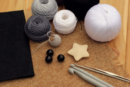 crochet hooks and balls of cotton thread on a wooden table, copy space.