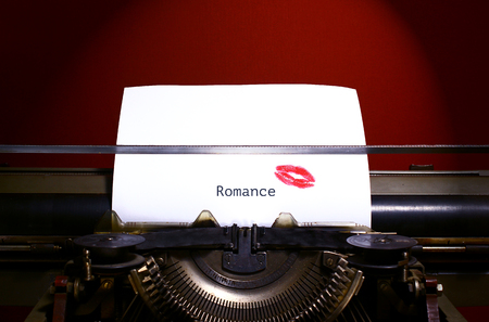 Romance title or heading typed in black ink on white paper on vintage manual typewriter. Red lipstick print on paper.