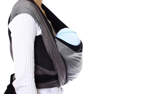 A newborn baby in blue hat in a ringsling baby carrier in vertical position