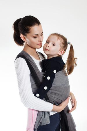 Una niña pequeña en la parte delantera cruzada lleva una envoltura en un portabebés tejido Foto de archivo