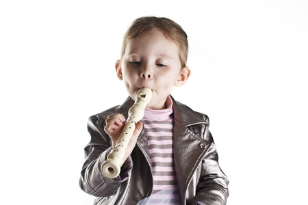 Portrait of a toddler girl playing on flute