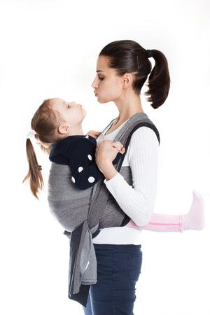 Divertida niña pequeña envuelta en posición frontal en un portabebés tejido