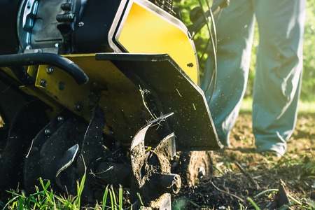 A close up view on motor cultivator during plow process spring season garden works concept Standard-Bild - 122826258