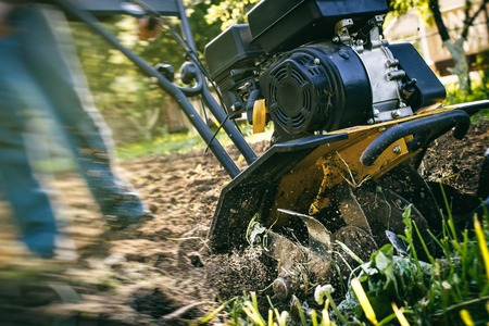 A close up view on motor cultivator during plow process spring season garden works concept
