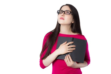 Smart young student woman in red shirt and glasses pressing black book to her heart, looking above on white background, knowledge woman concept idea