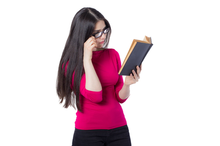Smart young student woman in red shirt and glasses reading black book holding in one hand, on white background, interested woman concept idea Banco de Imagens