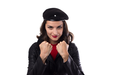 Young woman black jacket, red sweater and hat with a reference to  looking in camera, demonstrate her fists and smile on a white background with copy space