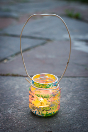 Colorful glass jar with wire handle candle lamp, kids activities and handmade idea concept vertical
