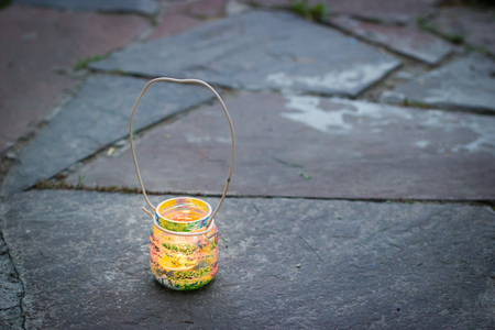Colorful glass jar with wire handle candle lamp, kids activities and handmade idea concept