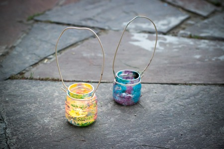 Two colorful glass jars with wire handle candle lamps on stone outdoor tile, kids activities and handmade idea concept