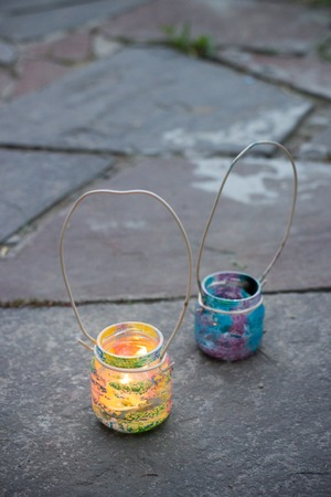 Two colorful glass jars with wire handle candle lamps on stone outdoor tile, kids activities and handmade idea concept vertical