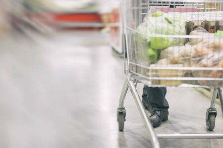 Man walk with cart between rows with refrigerators. shopping concept