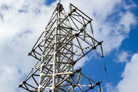 Hochspannungsmasten und Hochspannungsleitungen auf dem blauen Himmel und Wolkenhintergrund. Strommasten und ihre Silhouetten gegen den Nachthimmel.