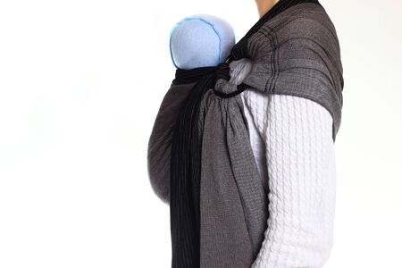 A newborn baby in a ringsling baby carrier in vertical position