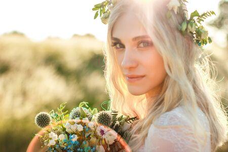 Bellissimo ritratto di giovane donna in un abito bianco in stile boho con una ghirlanda floreale in estate nel campo. Messa a fuoco morbida selettiva.