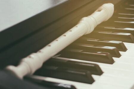 Block flute rest on a piano keyboard. classic music concept