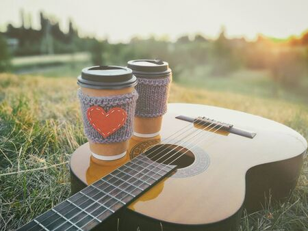 Two paper coffee cup in knitted cozy sleeves standing on guitar. Outdoor picnic sunset scene. Stock Photo