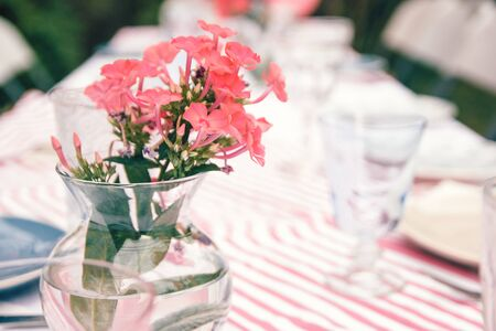 Rural wedding table decoration with coral flowers in a glass vase on a striped tablecloth. Special event table set up. Fresh flower decoration. Reklamní fotografie