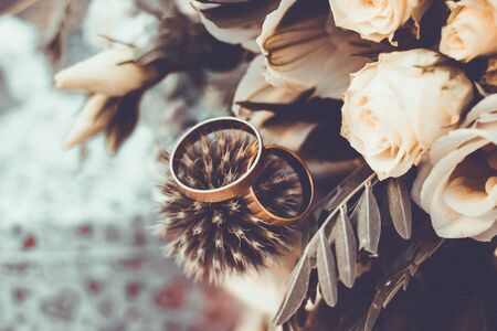 Close up view on wedding rings on rustic brides bouquet Stock Photo