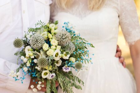 Rustic wedding bouquet in light yellow and braight tourquoise colour palette in summer sunny day