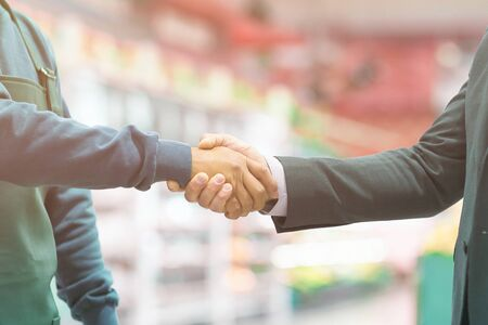 Business handshake employer and worker on blurred super market background Stock Photo
