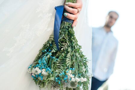 Back view on bride holding rustic wedding bouquet with tourquoise colour details and lens blurred groom on background Stock Photo