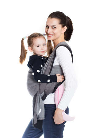 Mother tightening a woven baby wrap carrier with toddler girl in