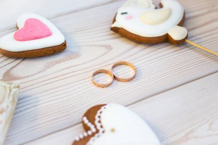 Close up view on heart shaped cookies bisquits on stick and wedding rings.