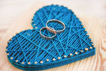 Close up view on string art heart with two wedding rings on it. Wedding decor concept idea
