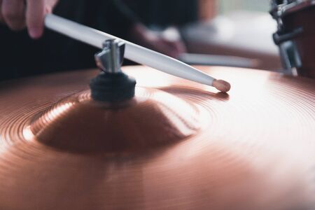 Close-up of a drummers hand holding white drum sticks while sitting behind a drum set. Stockfoto