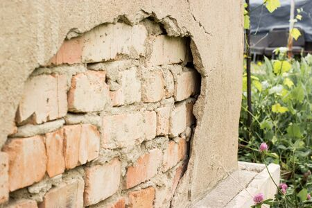 Non technology plaster. Building cracked plaster facade wall with brick.