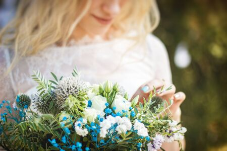 Beautiful blonde young bride portrait with flower bouquet and wreath on her head in white wedding dress outdoor in summer