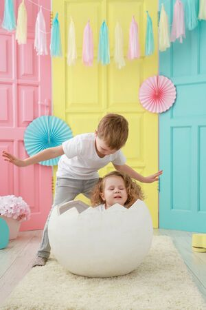 Older brother take care about his little sister is sitting in a white egg that hatched against a studio colorful background. Famly concept. Foto de archivo