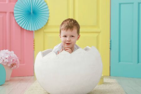 A little toddler kid boy is sitting in a white egg that hatched against a studio colorful background for a newborn portrait or family concept. Stock Photo - 135376942