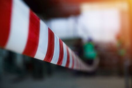 Red and white, striped protective tape protects the enclosed area, repair work. Industrial artistic blurred background around.