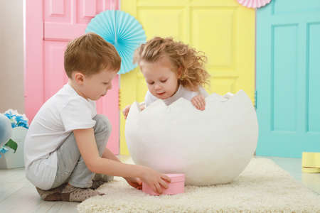 Pretty little blonde curly girl is sitting in a white egg and adorable blond boy portrait in white t-shirt on yellow, pink and blue background. Kid gender relations concept. 版權商用圖片