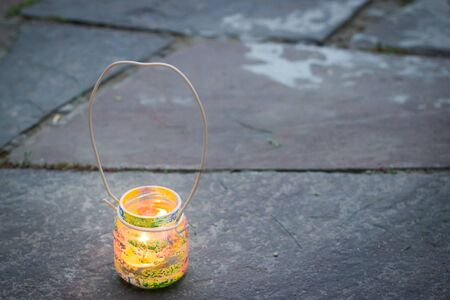 Colorful glass jar with wire handle candle lamp on stone outdoor tile, kids activities and handmade idea concept
