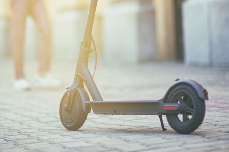 eco friendly transport electro scooter on city street tile in summer sunny day Stock Photo